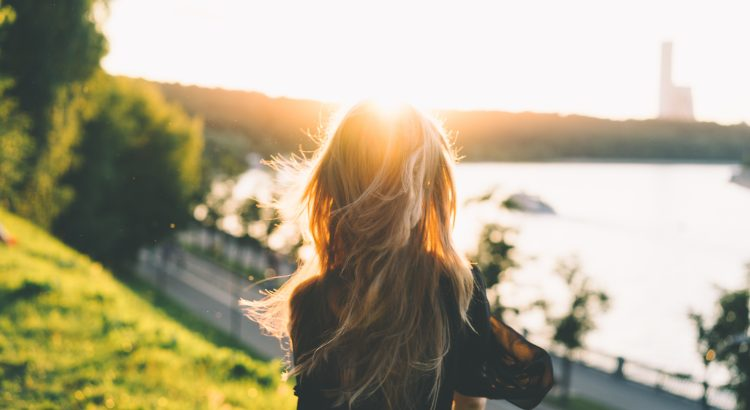 Back of a woman with long blond hair overlooking the ocean and mountains at sunset