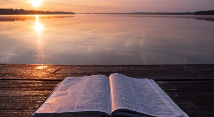 Open Bible on a wooden table with a large body of water and misty sunrise in the background