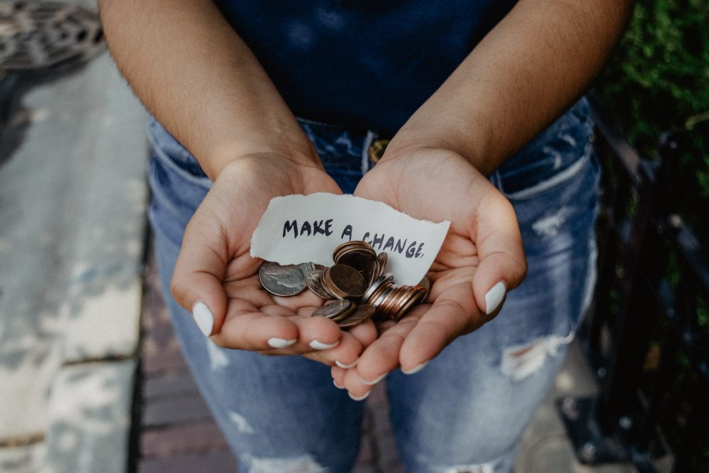 """Woman holding coins with a paper that says """"Make a Change."""""""