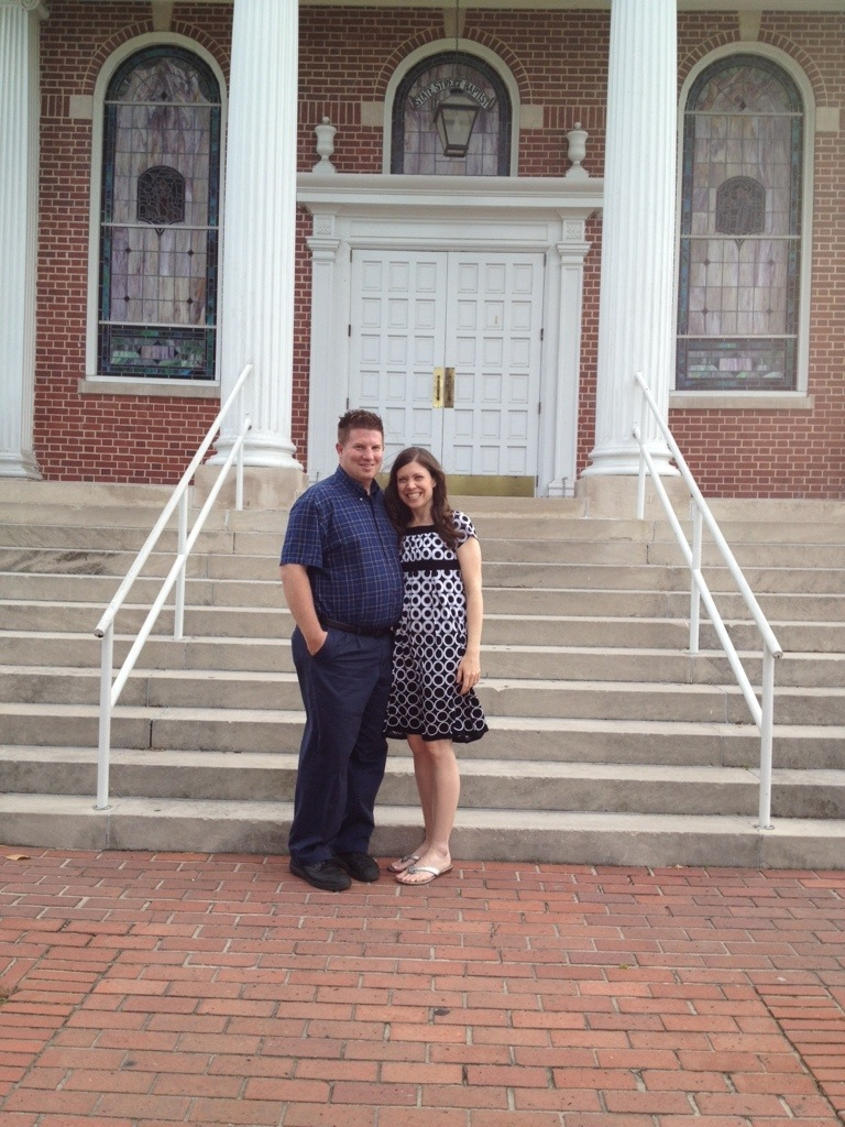 Christian wife and husband standing in front of the church steps where they were married years earlier