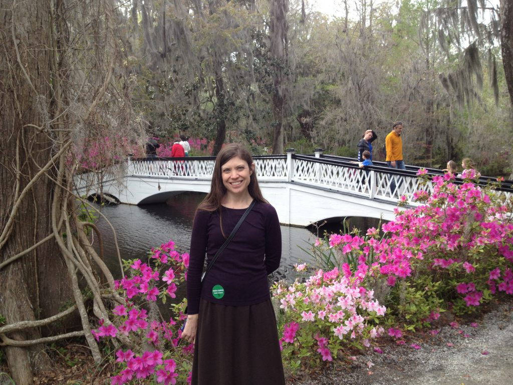 April Cassidy standing in front of a creek with a white bridge and azaleas blooming in the background
