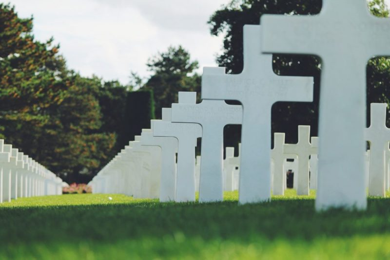ground level view of grass and many rows of white cross grave markers