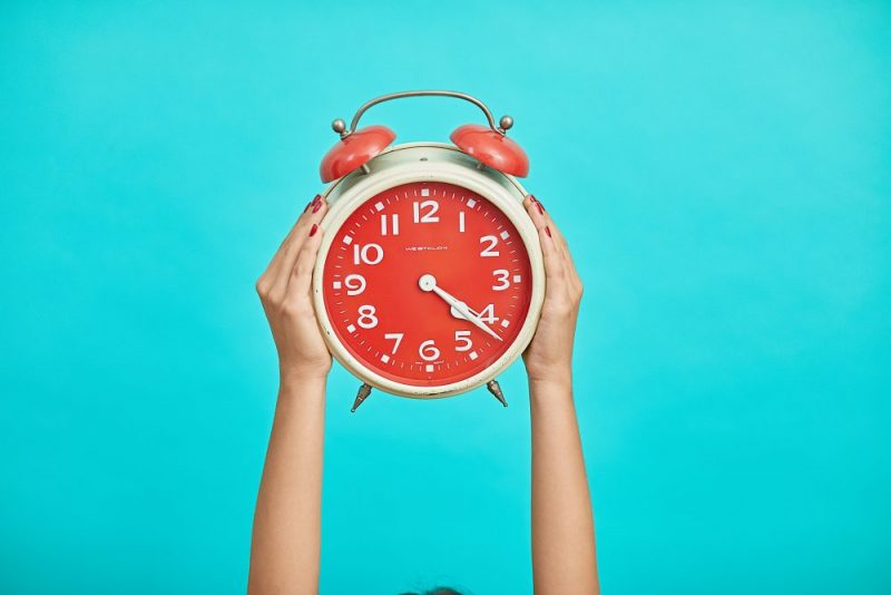 Red and white alarm clock with teal background