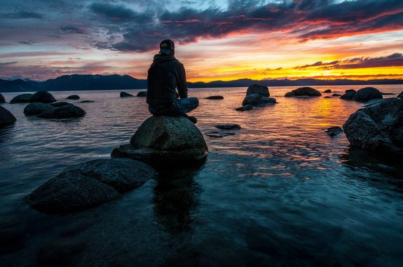 man sitting on rock in lake at surise