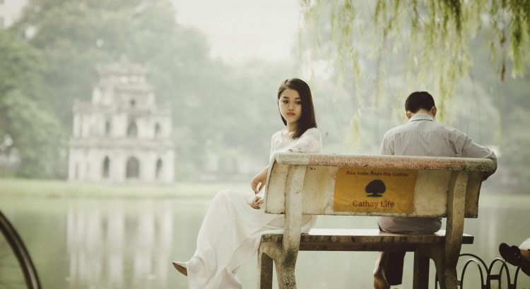 sad woman wearing white sitting on a park bench near a lake with a man