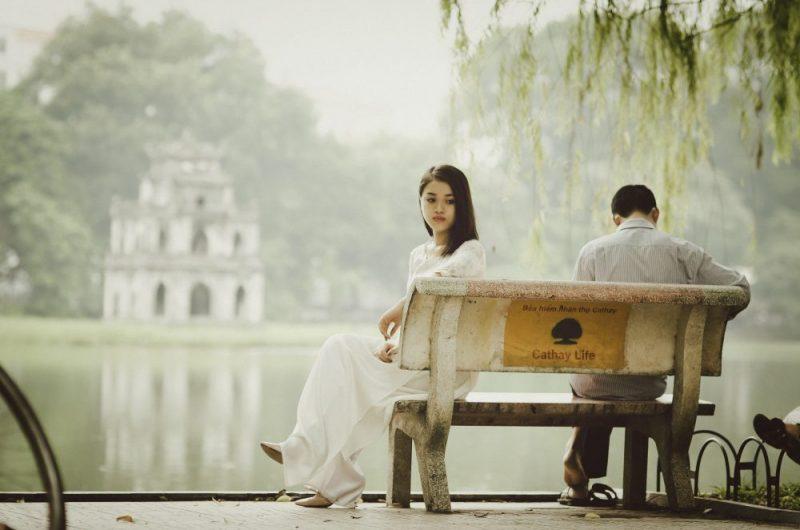 sad woman wearing white sitting on a park bench near a lake with a man