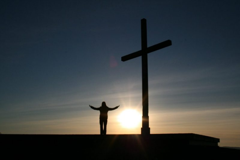 person standing before a cross at sunrise (preparing for persecution for our faith)