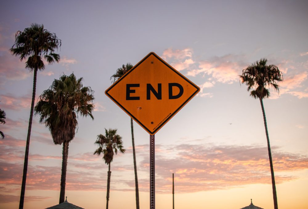 """Yellow diamond sign that says """"end"""" with sunset and palm trees in background"""